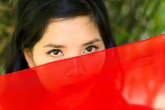 Въетнамская женщина peeking над красной тканью Стоковое Изображение