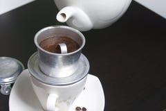 Въетнамская кофеварка оборудована на чашке Земной кофе полит в его Barista льет кипяток от чайника в его Стоковые Изображения