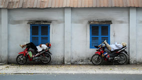 Въетнамский водитель такси мотоцилк спать на мотоцикле Стоковое Фото