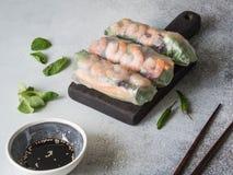 3 въетнамских блинчика с начинкой - моркови, огурец, салат мозоли, красная капуста, травы и креветки на деревянной темной доске С Стоковые Изображения