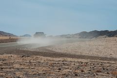Выберите вверх тележку управляя в сухой дороге пустыни и делая пыль Стоковые Фото