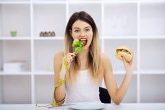 Выберите между высококалорийной вредной пищей против здорового питания стоковое фото