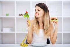 Выберите между высококалорийной вредной пищей против здорового питания стоковое изображение