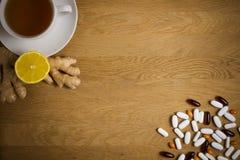 Выберите между традиционной и фольклорной медициной Чашка чаю, лимон, имбирь, различные пилюльки на деревянной предпосылке top стоковые фотографии rf