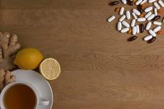 Выберите между традиционной и фольклорной медициной Чашка чаю, лимон, имбирь, различные пилюльки на деревянной предпосылке top стоковая фотография rf