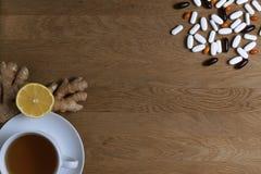 Выберите между традиционной и фольклорной медициной Чашка чаю, лимон, имбирь, различные пилюльки на деревянной предпосылке top стоковое изображение rf