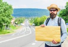 Выберите меня вверх Стойка автостопщика человека бородатая на крае дороги с знаком чистого листа бумаги, космосом экземпляра Преи стоковая фотография