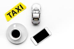Выберите такси в передвижном применении Ездите на такси ярлык, сотовый телефон, игрушка автомобиля на белом copyspace взгляд свер стоковые изображения