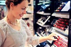 выбирает детенышей женщины магазина губной помады стоковая фотография rf