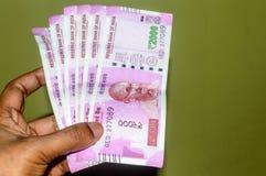 Выборочный фокус: Рука держа индийские 2000 примечаний рупии против изолированной предпосылки Закройте вверх новой банкноты 2000  стоковая фотография rf