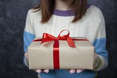 Выборочный фокус рук женщины держа подарочную коробку с красной лентой на день рождества и Нового Года или приветствуя сезон стоковые изображения rf