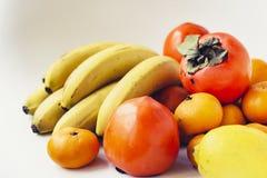 Выбор аранжированных различных свежих фруктов бананов, мандаринов, хурм и лимонов на белом конце предпосылки вверх стоковые фото