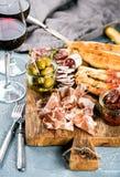 Выбор закуски мяса Салями, ветчина, ручки хлеба, багет, оливки и солнц-высушенные томаты, 2 стекла красного цвета Стоковое Изображение
