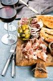Выбор закуски мяса Салями, ветчина, ручки хлеба, багет, оливки и солнц-высушенные томаты, 2 стекла красного цвета Стоковая Фотография