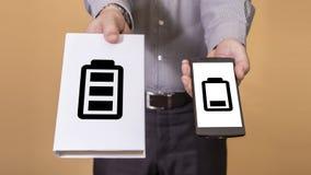 Выбор между книгой и временем работы от батарей мобильного телефона Стоковое фото RF