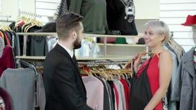 Выбор новой одежды Счастливые alluring красивые усмехаясь жизнерадостные взрослые пары выбирая новую одежду в магазине видеоматериал