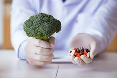 Выбор доктора предлагая между здоровой и витаминами Стоковые Изображения