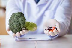 Выбор доктора предлагая между здоровой и витаминами Стоковое Изображение