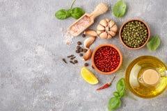 Выбор специй и трав - перца чеснока, соли, пинка, зеленых и черных, лимона, базилика, оливкового масла Ингридиенты для варить Стоковые Фото