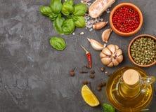 Выбор специй и трав - перца чеснока, соли, пинка, зеленых и черных, лимона, базилика, оливкового масла Ингридиенты для варить Стоковое фото RF