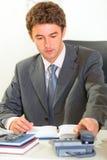 выбор телефона офиса стола бизнесмена сидя вверх Стоковое Изображение