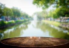 Выбранный деревянный стол фокуса пустой и взгляд нерезкости природы реки Стоковая Фотография