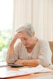 Выбытая женщина высчитывая ее отечественные векселя Стоковые Фотографии RF