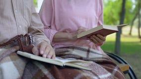 Выбытые книги чтения пар, скамейка в парке усаживания совместно, часы досуга пенсии видеоматериал