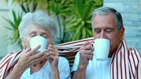 Выбытые пары наслаждаясь кофе снаружи