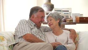 Выбытые старшие пары сидя на софе дома совместно видеоматериал