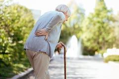 Выбытый больной backache чувства женщины в парке Стоковое фото RF