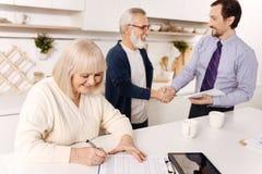 Выбытый контракт женщины подписывая пока ее супруг приветствуя нотариуса Стоковая Фотография RF