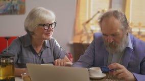 Выбытый пенсионер делая приобретение кредитной карточки в уютном кафе рядом с женщиной старости сток-видео