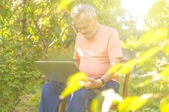 Выбытый пенсионер используя современные приборы технологии на курорте летних каникулов стоковые фото