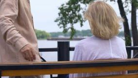 Выбытый человек обнимая жену сидя на скамейке в парке около реки, старшие пары отдыхает акции видеоматериалы