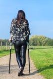 Выведенная из строя женщина идет на костыли в голландской природе стоковая фотография