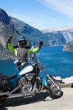 Выведенные из glads мотоциклиста женщины, который будет путешествовать мотоцикл в Норвегии, Скандинавии Точка зрения с северными  стоковая фотография