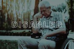 Выведенный из строя в кресло-коляске Задумчиво сидя пенсионер стоковое изображение