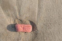 Выветренный булыжник на песке пляжа стоковое изображение rf