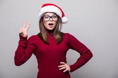 Выведенная девушка рождества с пальцем шляпы santa вверх Стоковые Изображения