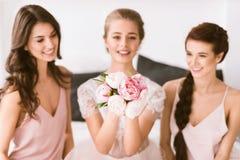 Выведенная невеста сидя в спальне с ее bridesmaids Стоковое Изображение