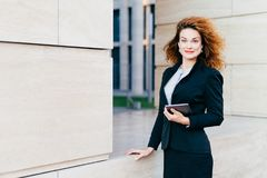 выглядящая Приятн женщина одела официально, держащ цифровой планшет который необходим для ее работы Красивая женщина с дворняжкой стоковое изображение