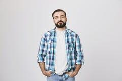 выглядящий Уверенно парень с усиком и борода, держа руки в карманн и смотря камеру, над серой предпосылкой стоковое фото rf