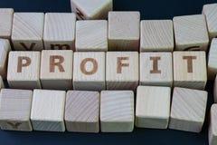 Выгода в invesment, доходе компании или концепции финансового дохода, блоке куба деревянном с комбайном алфавита выгода слова на  стоковые фото