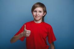 выглядящий Европейск мальчик 10 лет больших пальцев руки вверх дальше Стоковая Фотография RF