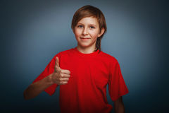 выглядящий Европейск мальчик 10 лет больших пальцев руки вверх на a Стоковые Изображения