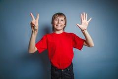 выглядящий Европейск мальчик 10 лет показывает номер Стоковое Фото