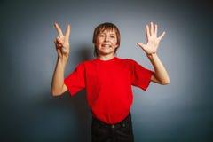 выглядящий Европейск мальчик 10 лет показывает номер Стоковая Фотография