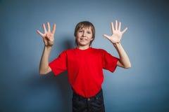 выглядящий Европейск мальчик 10 лет показывает число 9 Стоковые Фотографии RF