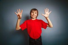 выглядящий Европейск мальчик 10 лет показывает число 9 Стоковая Фотография RF